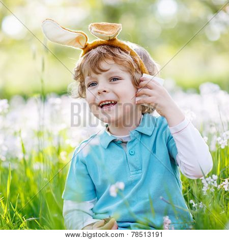 Cute Happy Little Child Wearing Easter Bunny Ears At Spring Green Grass