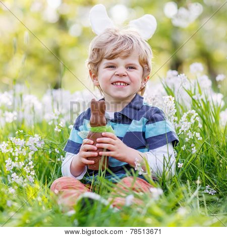Little Toddler Wearing Easter Bunny Ears And Eating Chocolate At Spring Green Grass
