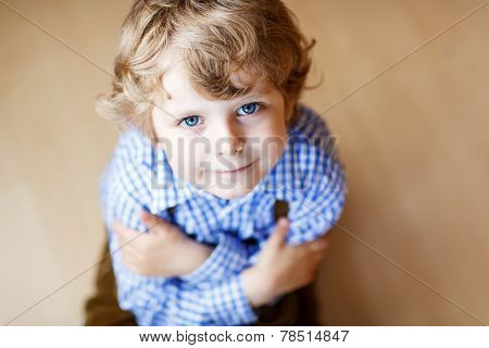 Portrait Of Adorable Little Boy With Blond Hairs And Blue Eyes