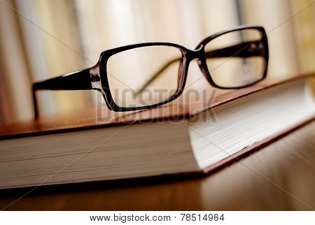 Eyeglasses On Top Of The Book