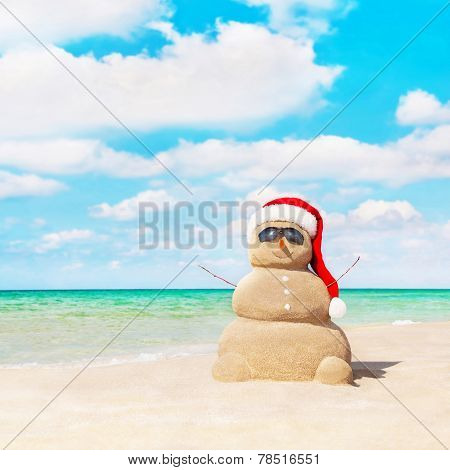 Sandy Snowman In Santa Hat At Beach. Christmas Concept