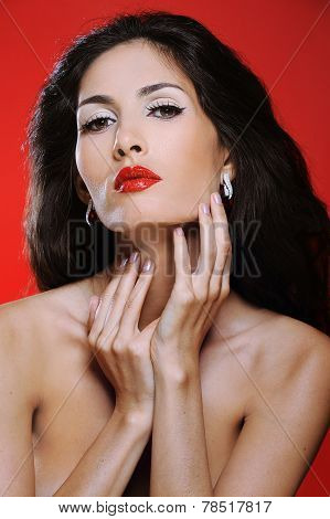 Attractive brunette woman with magnificent hair on red background touches her neck