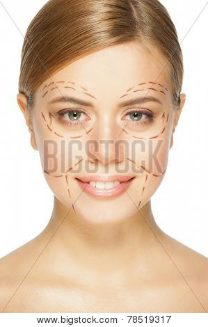 Beautiful young caucasian woman with perforation lines on her face before plastic surgery operation. Beautician touching woman face.