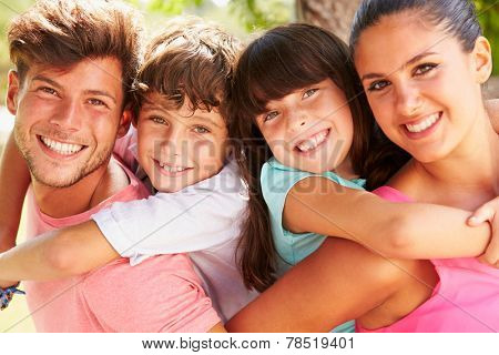 Parents Giving Children Piggyback Ride Outdoors