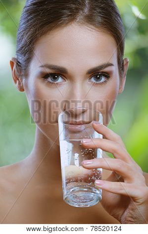 Beautiful girl Drinks Cold Mineral Water From Glass