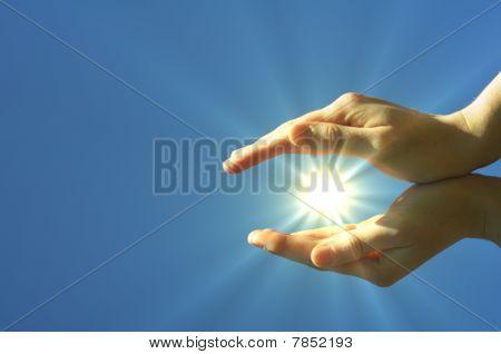 Mano sol y cielo azul