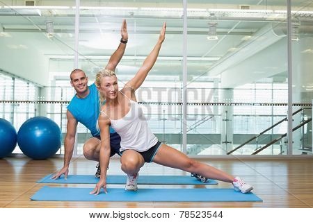 Portrait of happy young couple stretching hands in yoga class