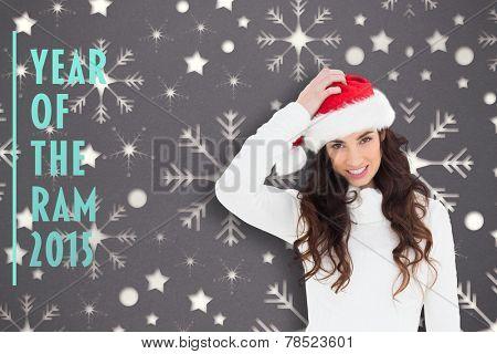 Confused brunette in santa hat against snowflake wallpaper pattern