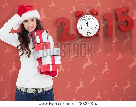 Stressed brunnette in santa hat holding gifts against orange reindeer pattern