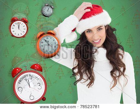 Confused brunette in santa hat against green christmas tree pattern