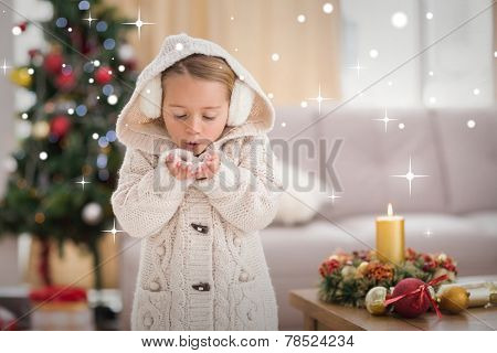 Festive little girl blowing over hands against snow