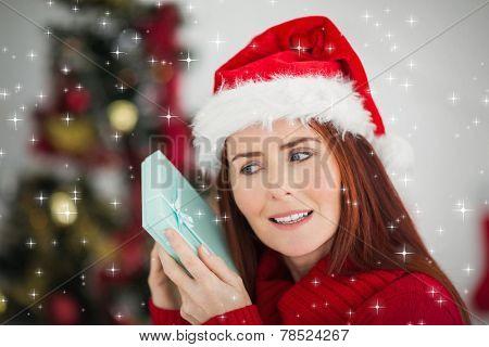 Festive redhead holding christmas gift against snow