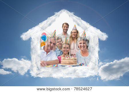 Cheeful family smiling at camera at birthday party against cloudy sky with sunshine