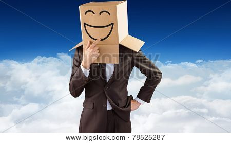 Anonymous businessman touching his chin against bright blue sky over clouds