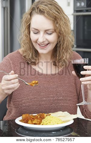 Woman Eating Takeaway Curry And Drinking Wine
