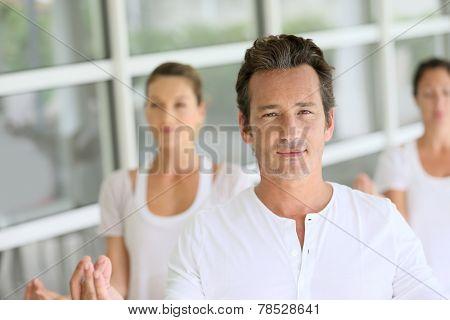 Mature man amongst group doing yoga exercises