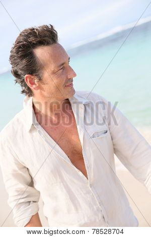 Handsome 40-year-old man walking on beach