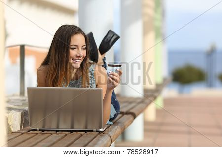 Casual Girl Buying Online With A Credit Card Outdoors