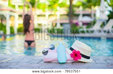 Suncream, hat, sunglasses, flower and tower near swimming pool