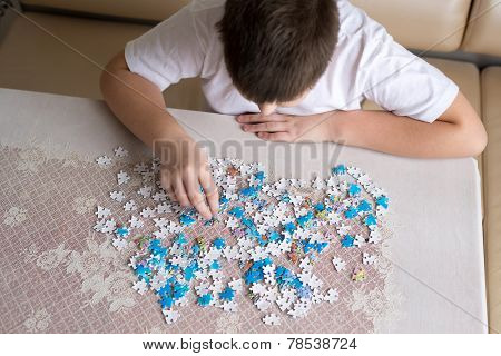 Teenager Boy Collects Puzzles At  Table