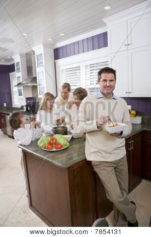 Man Eating In Kitchen With Family In Background