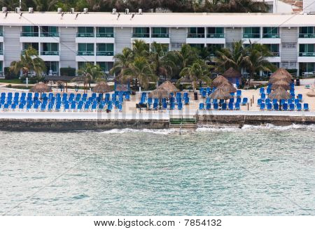 Blue Chairs At Seawall By Hotel