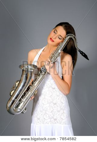 Portrait Of Elegant Woman In White Dress Holding Saxophone. Gray Background