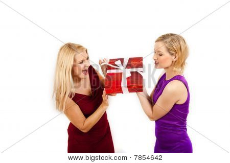 Two beautiful party girls holding one big red present
