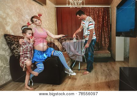 Pregnant woman with her daughter watching TV, while her husband irons a shirt  in the living room