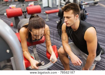 sport, fitness, lifestyle and people concept - young woman and personal trainer flexing leg muscles on gym machine