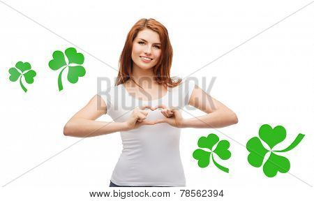 gesture, holidays, st. patricks day and happy people concept - smiling girl in white blank t-shirts showing heart with hands over white background with green shamrock or clover