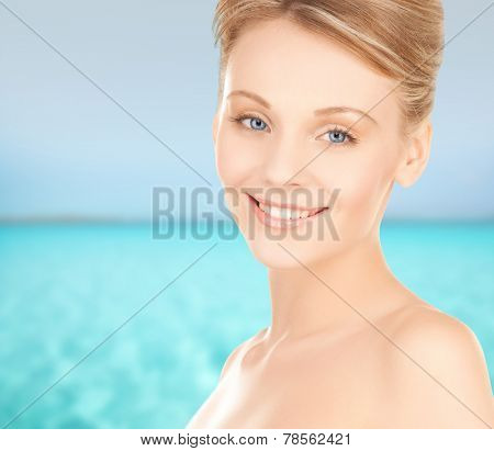 beauty, people and health concept - beautiful young woman face over blue sea and sky background