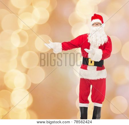 christmas, holidays, gesture and people concept - man in costume of santa claus over beige lights background
