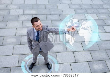 global business, development, technology and people and concept - young smiling businessman pointing finger to virtual globe projection outdoors from top