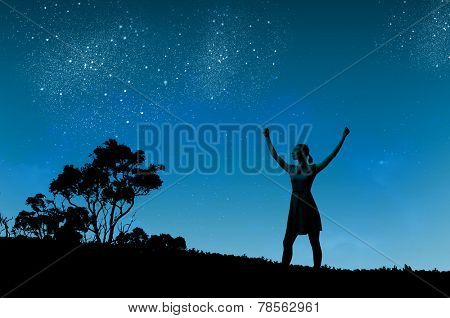 Silhouette of woman in dress at night with hands up