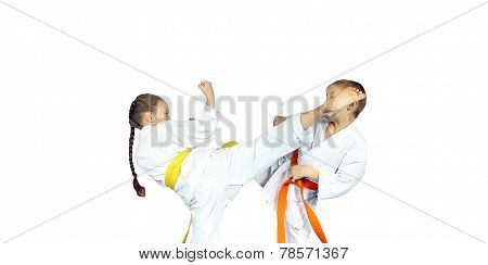 Little girl athlete in karategi  is beating to athlete leg on the head