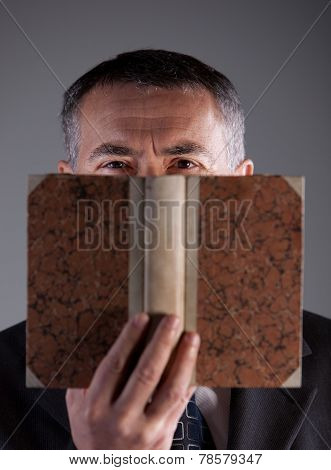 Mature Man Behind An Ancient Book
