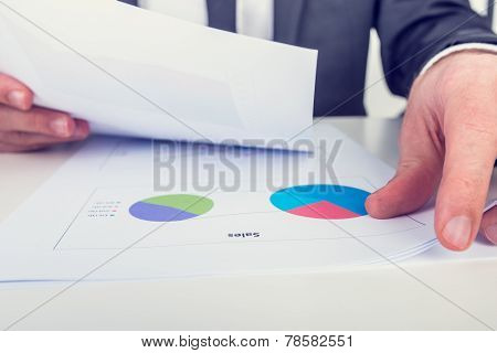 Retro Image Of The Hands Of A Businessman Analysing A Set Of Pie Graphs