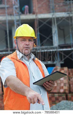 Builder in yellow helmet with document