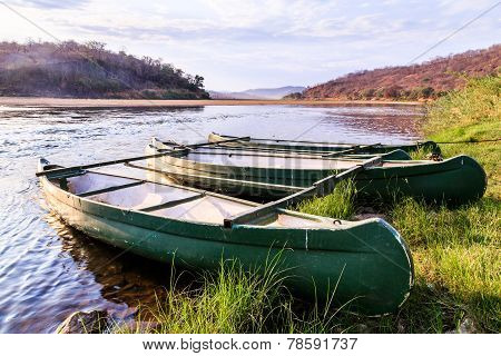 Rowing Boat Lying On The Banks Of A River Lit By Sun