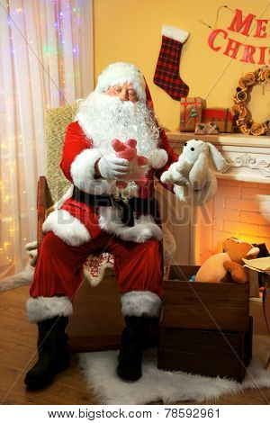 Santa Claus sitting with presents in comfortable chair near fireplace at home