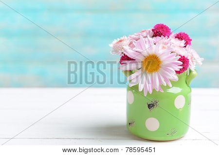 Beautiful flowers in cans on table on light blue background