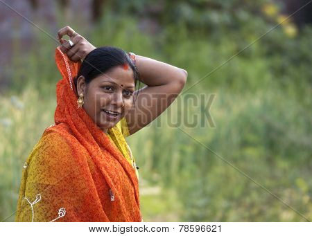 Young Woman Covers Her Hair With Orange Sari.