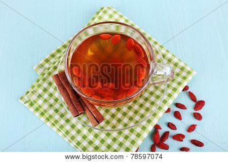Goji berries drink in glass cup and cinnamon on glass saucer on green checkered napkin on light blue background
