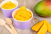 stock photo of vegan  - Serving of frozen homemade creamy ice yoghurt with fresh mango and wooden spoon - JPG