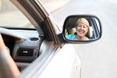 senior woman looking in side mirror