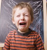 stock photo of crying boy  - little cute boy screaming and crying at school near blackboard - JPG