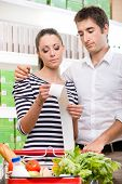 stock photo of receipt  - Young couple at supermarket checking a long receipt with shopping cart on foreground - JPG