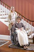 Постер, плакат: Старший женщина в инвалидной коляске дома с медсестра