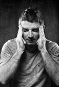 stock photo of suffering  - young man suffering migraine and headache in intense pain feeling desperate and sick with hands on tempo in stress isolated on studio background black and white - JPG